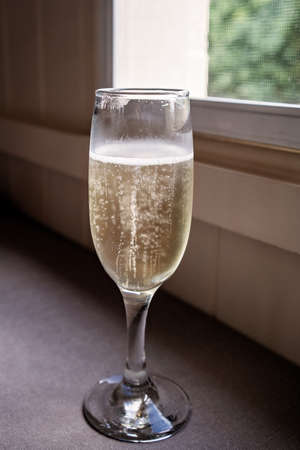 A glass of sparkling wine placed near a window to catch the light in the bubbles