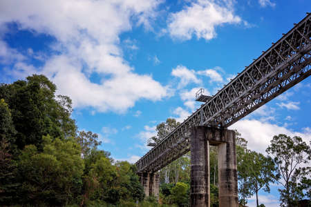 A concrete and steel railway bridge over a country river against a cloudy blue sky