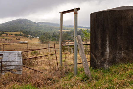 A concrete water tank and old broken down fencing on a run down dairy property 写真素材