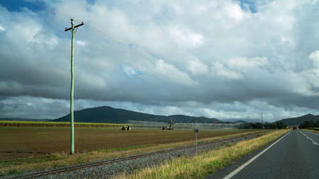 A farmer irrigating his field of sugar cane growing by the side of the road