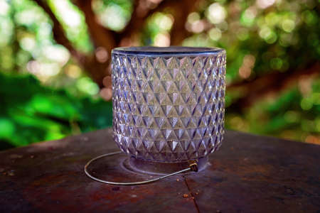 An upside down vintage glass candle holder against a blurred garden background