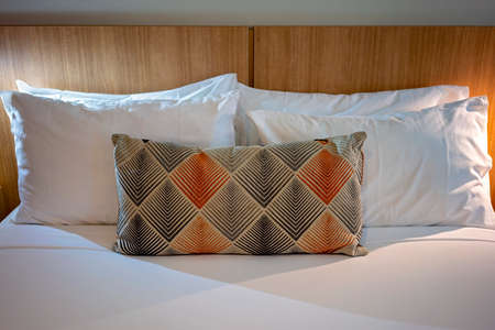 Bed in a hotel room with stacked pillows and a decorative pillow