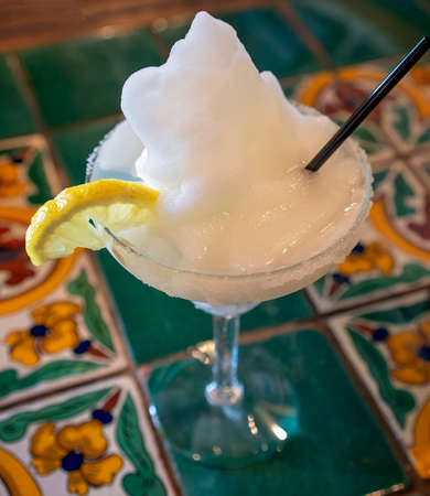 An iced tequila margarita cocktail with straw and slice of lemon in a salt rimmed glass sitting on a decorative table at a restaurant