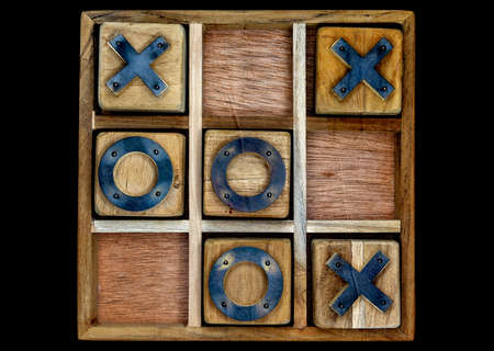 A wooden game set of noughts and crosses on a black background, also known as tic-tac-toe Imagens