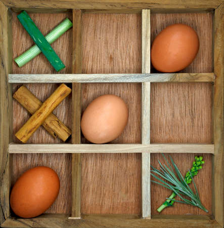 A wooden game set of noughts and crosses using eggs as the noughts and herbs as the crosses