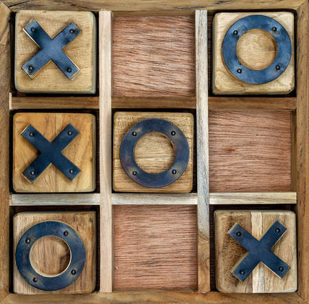 A wooden game set of noughts and crosses on a black background, also known as tic-tac-toe