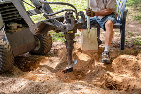 A mechanical auger digging holes in the soil with the aid of a senior male with a shovel 写真素材