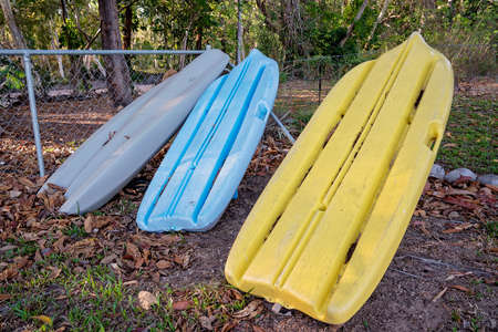 Kayaks leaning against a fence in a rural backyard on a creek bank