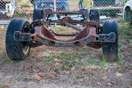 An old car chassis discarded in a rural backyard Stock Photo