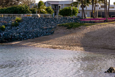 A small beach beside a marina seawall and in front of the oceanfront residential precinct in late afternoon shadows