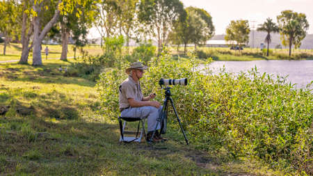 Mackay, Queensland, Australia - January 2021: Male retiree photographer taking photos of birds on a pond in late afternoon sunlight. Redactioneel