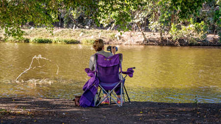 Mackay, Queensland, Australia - January 2021: Female retiree photographer taking photos of birds on a pond in late afternoon sunlight.