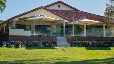 Mackay, Queensland, Australia - January 2021: Residential home with expansive glass enclosed sundeck and geese in the front yard