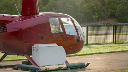 Airlie Beach, Queensland, Australia - February 2021: A red helicopter parked beside the airport runway 新闻类图片