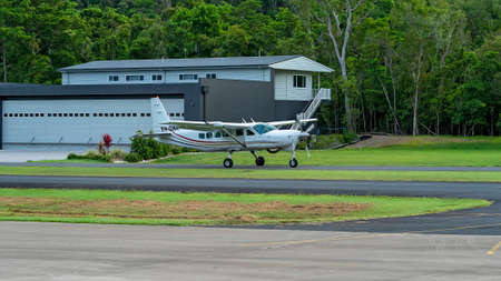 Airlie Beach, Queensland, Australia - February 2021: A light aircraft filled with skydivers taxiing along the runway prior to takeoff