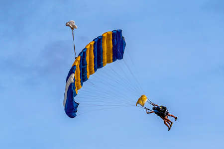 Airlie Beach, Queensland, Australia - February 2021: Tandem skydivers with parachute open coming into land