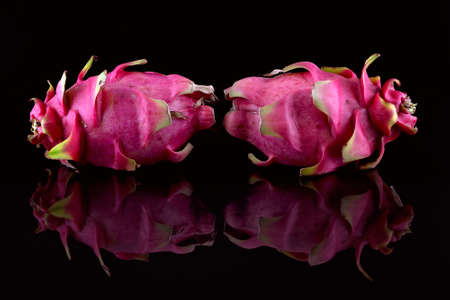 Two dragon fruit placed on the edge of a black tank of water to catch the reflections