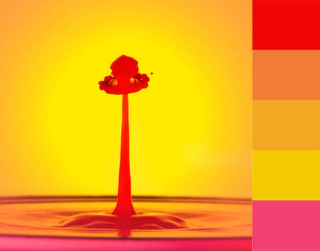 A red water drop spout with a decorated hat shape on top, against a yellow background. Liquid drop art, water drop photography - color theme included 免版税图像