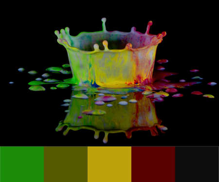 A drop of milk released from above into tiny spots of colourful paint to create a crown shape on a shiny black surface with a reflection - color theme included 免版税图像