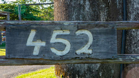 A timber sign with the property number etched into the wood 免版税图像