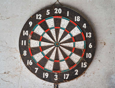 An old well used dart board covered with cobwebs nailed to a wall