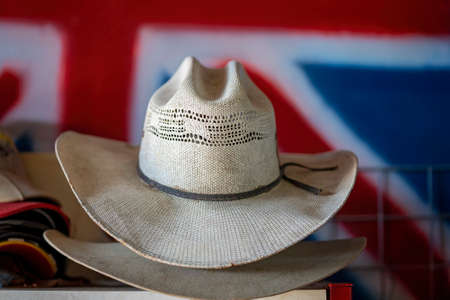 Old hat collection against a background of the colours of the Australian flag