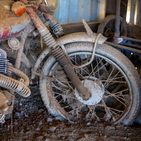 Closeup of the front wheel of a rusted vintage motorcycle covered in dirt and cobwebs