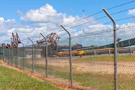 Mackay, Queensland, Australia - March 2021: Coal export terminal machinery secured behind high fence 新闻类图片