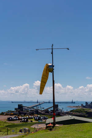 Mackay, Queensland, Australia - March 2021: A yellow windsock to measure wind speed and direction against a clear sky