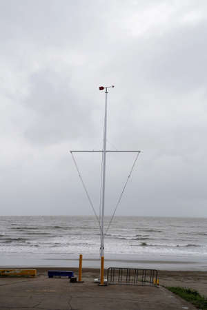 Weather vane and mast frame on the beach at a yacht club on a rainy day 免版税图像
