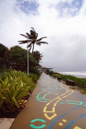 A colorfully painted footpath leading into the distance beside the ocean on a wet and cloudy day