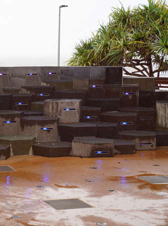 A group of stepping blocks highlighted with colored lights, motion activates water sprays 免版税图像