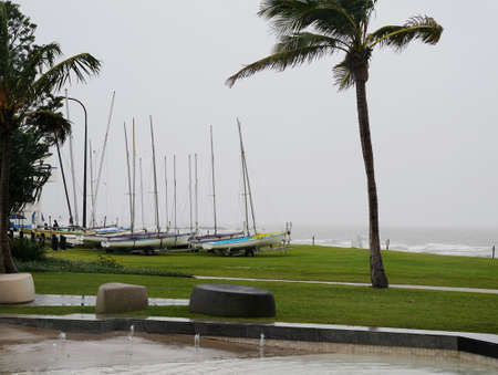 Small sailing yachts on trailers parked on grass beside the ocean on a wet and windy day 免版税图像