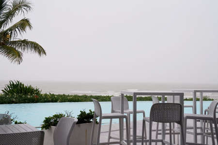 Cafe tables and chairs beside an infinity pool by the ocean on a wet and windy grey overcast day