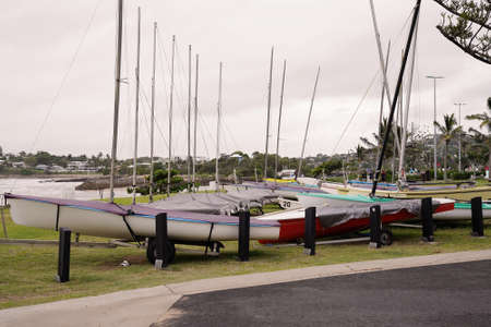 Small sailing yachts parked on their trailers on a grassy patch by the ocean on a rainy overcast day 免版税图像
