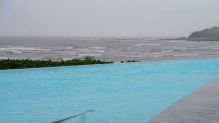 An infinity pool by the ocean on a wet and rainy grey overcast day 免版税图像