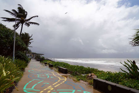 A public colorfully painted footpath leading into the distance beside the ocean on a wet and cloudy day