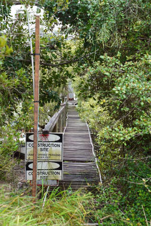 Construction site signage onto an old falling down jetty leading amongst bushland to a creek