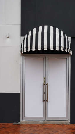 Front door with black and white striped canvas awning