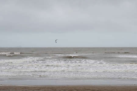 A lone windsurfer battling the waves on a rainy overcast and windy day