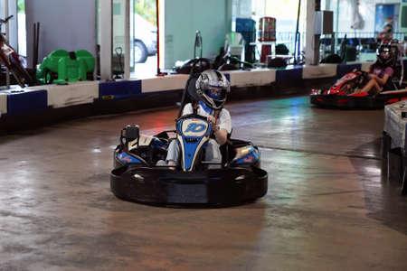 Mackay, Queensland, Australia - April 2021: A woman drives a go-kart in a fun recreational drive around a circuit in public Редакционное