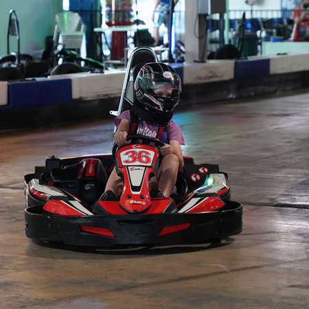 Mackay, Queensland, Australia - April 2021: A young girl drives a go-kart in a fun recreational drive around a circuit in public