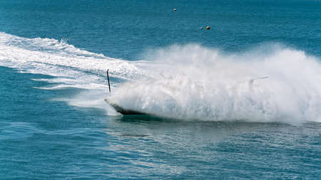 Thick ocean spray hides a spinning jet boat full of tourists enjoying their adrenaline ride
