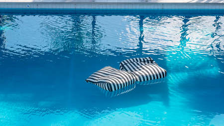 Floating Cushions available for guest use in the pool at a luxury resort hotel Фото со стока