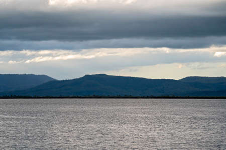 View across the water to the dam wall and beyond to the mountains and a stormy sky