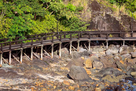 A long wooden elevated walking track along a rocky beach shoreline