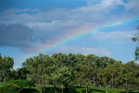 A colorful rainbow in the cloudy sky over the treed banks of a dam