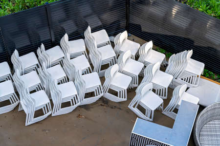 White plastic chairs stacked in a yard outdoor at a resort hotel for later use Фото со стока