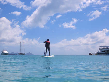 Whitehaven Beach, Whitsundays, Queensland, Australia - April 2021: Male in stinger suit standing on a surfboard paddle board with tourist boats background