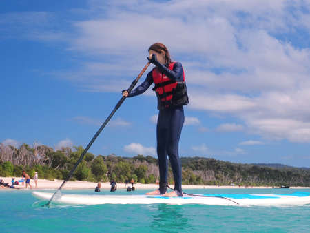 Whitehaven Beach, Whitsundays, Queensland, Australia - April 2021: Young woman standing on paddle board in front of white silicon sand beach with people enjoying outdoors